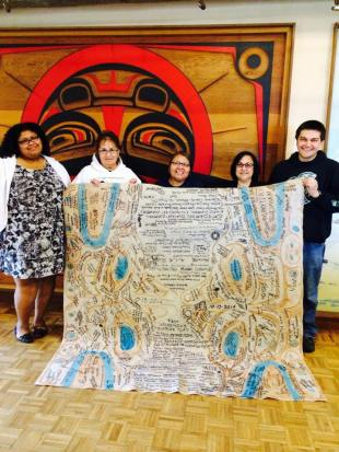 Day Break Star staff with donated blanket that includes the names of all those who attended Seattle's 1st Indigenous Peoples' Day celebration.