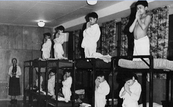 Children prayed many times a day. In 1950, Swampy Cree boys kneel before bedtime with an Anglican supervisor looking on, at Bishop Horden Memorial School on Moose Factory Island, On._http://www.coha.org/residential-schools-canadas-inglorious-educational-past/_Source : Shingwauk Residential Schools Centre